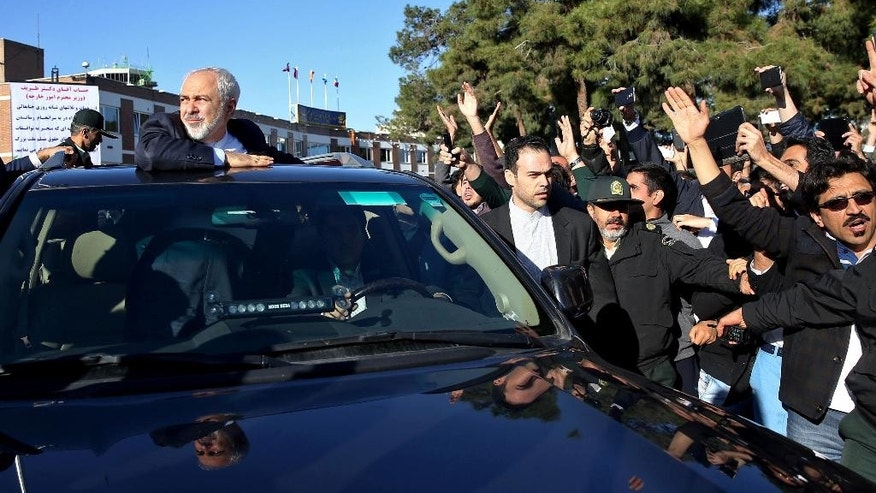 Iranian Foreign Minister Mohammad Javad Zarif, who is also Iran's top nuclear negotiator, looks at his well wishers upon arrival at the Mehrabad airport in Tehran, Iran, from Lausanne, Switzerland, Friday, April 3, 2015. Iran and six world powers reached a preliminary nuclear agreement Thursday outlining commitments by both sides as they work for a comprehensive deal aiming at curbing nuclear activities Tehran could use to make weapons and providing sanctions relief for Iran. (AP Photo/Ebrahim Noroozi)