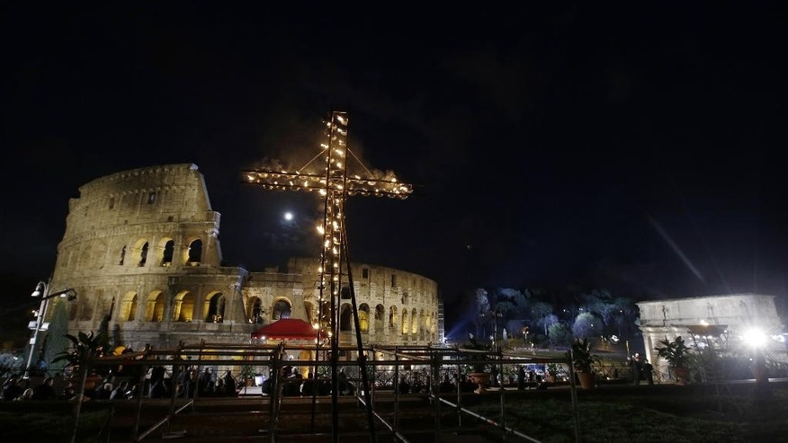 A cross faces the Colosseum as a full moon rises over it before the start of the Via Crucis (Way of the Cross) torchlight procession to be celebrated by Pope Francis on Good Friday in Rome, Friday, April 3, 2015. (AP Photo/Gregorio Borgia)
