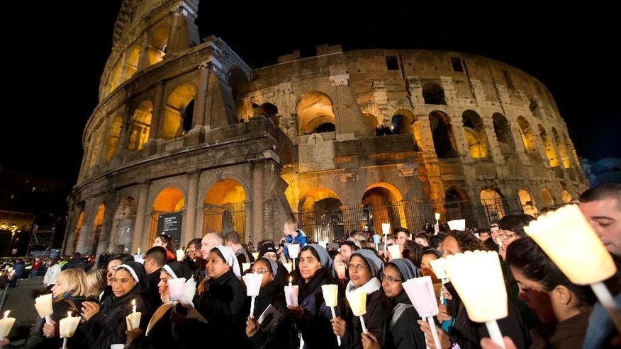 Nuns and faithful hold candles as they attend the Via Crucis (Way of the Cross) torchlight procession celebrated by Pope Francis in front of the Colosseum on Good Friday, in Rome, Friday, April 3, 2015. (AP Photo/Andrew Medichini)