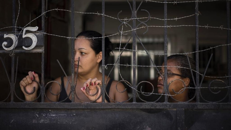Women watch police patrol from behind their home's wired fence inside the Alemao slum complex in Rio de Janeiro, Brazil, Friday, April 3, 2015. Intense violence is once again gripping one of Rio de Janeiro's largest complex of slums, with several suspects and bystanders shot, including a 10-year-old boy, as gangs and police exchange intense gunfire. (AP Photo/Felipe Dana)