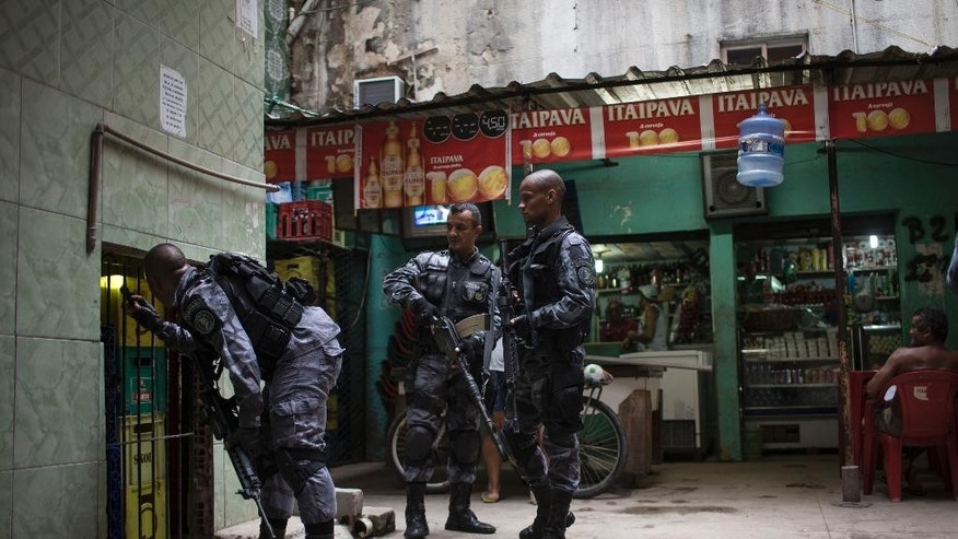 Military police officers search for drugs and weapons at the Roquette Pinto shantytown, part of the Mare slum complex in Rio de Janeiro, Brazil, Wednesday, April 1, 2015. The Brazilian army has begun to pull out of one of Rio de Janeiro's most violent slums, with police assuming responsibility for security in the area. (AP Photo/Felipe Dana)