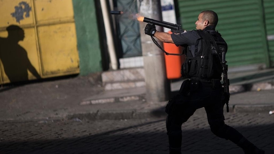 A police officer fires tear gas towards protesters at the end of demonstration calling attention to the violence that erupts during police operations against suspected drug traffickers, in the Alemao slum complex in Rio de Janeiro, Brazil, Friday, April 3, 2015. Residents were protesting the shooting deaths of a young boy and a 41-year-old housewife, who were killed by stray bullets in the past few days. Some protesters briefly clashed with police after the rally. The protesters hurled rocks and bottles while police officers responded with tear gas and stun grenades. (AP Photo/Felipe Dana)