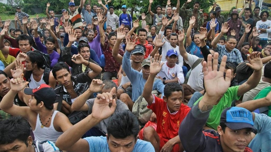Burmese fishermen raise their hands as they are asked who among them wants to go home at the compound of Pusaka Benjina Resources fishing company in Benjina, Aru Islands, Indonesia, Friday, April 3, 2015. Hundreds of foreign fishermen on Friday rushed at the chance to be rescued from the isolated island where an Associated Press report revealed slavery runs rampant in the industry. Indonesian officials investigating abuses offered to take them out of concern for the men's safety. (AP Photo/Dita Alangkara)