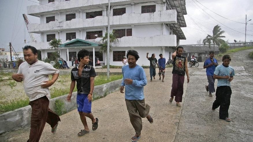Burmese fishermen run to collect their belongings after being informed that they can leave, at the compound of Pusaka Benjina Resources fishing company in Benjina, Aru Islands, Indonesia, Friday, April 3, 2015. Hundreds of foreign fishermen on Friday rushed at the chance to be rescued from the isolated island where an Associated Press report revealed slavery runs rampant in the industry. Indonesian officials investigating abuses offered to take them out of concern for the men's safety. (AP Photo/Dita Alangkara)