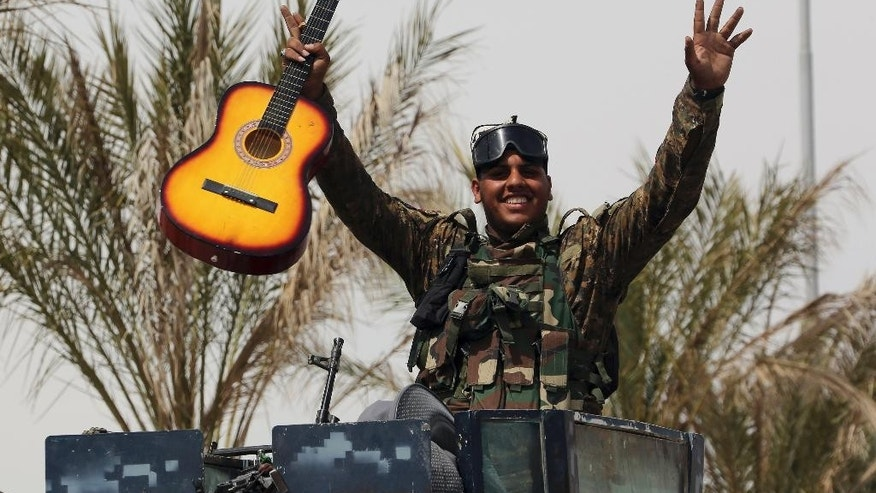 An Iraqi soldier celebrates with his guitar atop his armored vehicle on the main road between Baghdad and Tikrit, 80 miles (130 kilometers) north of Baghdad, Iraq, Friday, April 3, 2015. (AP Photo/Khalid Mohammed)