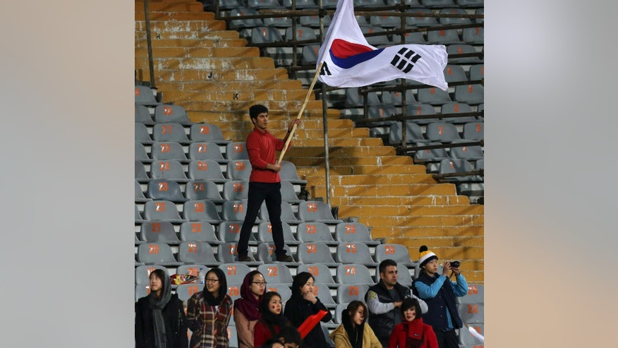FILE - In this Nov. 18, 2014 file photo, a soccer fan waves a South Korean flag as South Korean spectators stand below, during a friendly soccer match with Iran at the Azadi, (freedom) stadium in Tehran, Iran. Iranian authorities have partially lifted a ban on women attending men's sports matches, a senior sports official said Saturday, April 4, 2015. In the past, exceptions have been granted to allow foreign women living in Iran to attend matches by their visiting national teams. (AP Photo/Vahid Salemi, File)