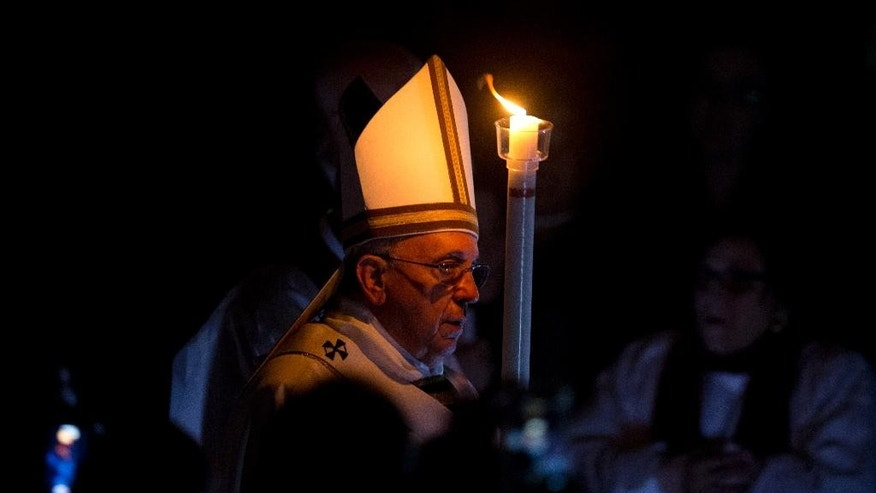 Pope Francis holds a lit white candle as he arrives for an Easter vigil service, in St. Peter's Basilica, at the Vatican, Saturday, April 4, 2015. (AP Photo/Andrew Medichini)