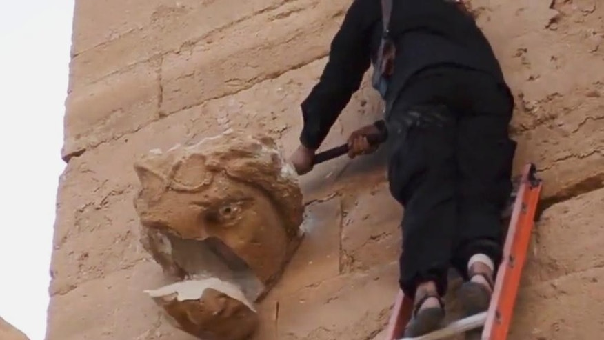 In this image made from a militant video posted on YouTube on Friday, April 3, 2015, which has been verified and is consistent with other AP reporting, a piece falls off from a curved face on the wall of an ancient building as a militant hammers it in Hatra, a large fortified city recognized as a UNESCO World Heritage site, 110 kilometers (68 miles) southwest of Mosul, Iraq. (AP Photo/Militant video)