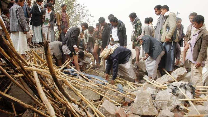Yemenis search for survivors in the rubble of houses destroyed by Saudi-led airstrikes in a village near Sanaa, Yemen, Saturday, April 4, 2015. Since their advance began last year, the Shiite rebels, known as Houthis have overrun Yemen's capital, Sanaa, and several provinces, forcing the country's beleaguered President Abed Rabbo Mansour Hadi to flee the country. The Saudi-led coalition continued to carry out intensive airstrikes overnight and early Saturday morning targeting Houthi positions. (AP Photo/Hani Mohammed)