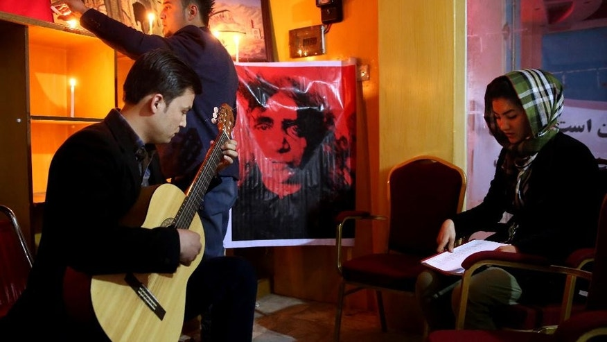 In this Tuesday, March 31, 2015 photo, an independent artist plays the guitar during a memorial ceremony for  27-year-old Farkhunda, an Afghan woman who was beaten to death by a mob last month, in Kabul, Afghanistan. Poets, musicians, actors and activists gathered this week to commemorate the short life and violent death of a woman who has become a symbol for justice and women's rights in a country that historically elevates warlords and battlefield heroes to national icons. (AP Photo/Massoud Hossaini)
