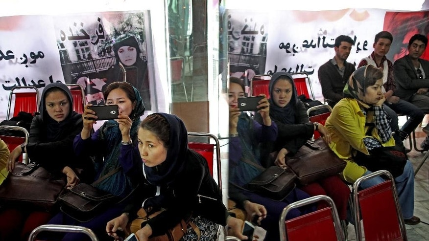In this Tuesday, March 31, 2015 photo, Afghan poets and independent artists listen to poems during a memorial ceremony for 27-year-old Farkhunda, an Afghan woman who was beaten to death by a mob last month, in Kabul, Afghanistan. Poets, musicians, actors and activists gathered this week to commemorate the short life and violent death of a woman who has become a symbol for justice and women's rights in a country that historically elevates warlords and battlefield heroes to national icons. (AP Photo/Massoud Hossaini)