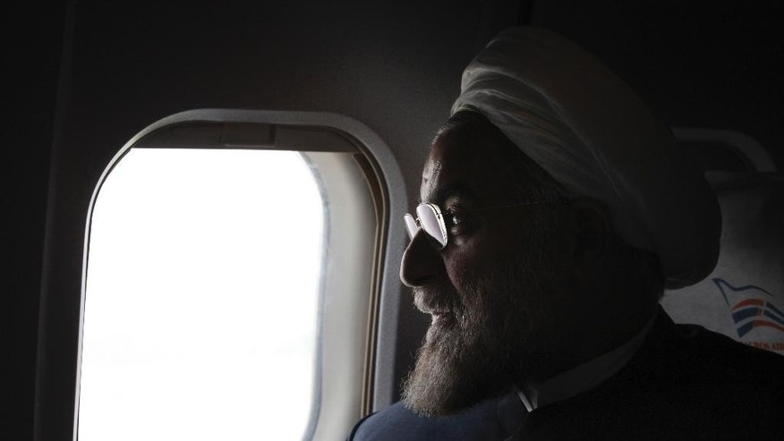 FILE - In this Monday, June 10, 2013, photo, Iranian President-elect Hassan Rouhani, a former Iran's top nuclear negotiator, looks on in his plane during his presidential election campaign tour to northwestern Iran. If, as critics contend, the nuclear framework deal between world powers and Tehran ends up projecting U.S. weakness instead, that could embolden rogue states and extremists alike, and make the region's vast array of challenges even more impervious to Western intervention. (AP Photo/Vahid Salemi, File)