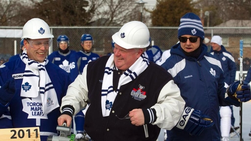 FILE - Toronto Mayor Rob Ford, center, smiles as he officially opens the refurbished Sunnydale rink with Toronto Maple Leafs' coach Ron Wilson, right, and other dignitaries who were on hand as well as the Toronto Maple Leafs NHL hockey team, who practiced on the outdoor rink in Toronto in this Wednesday, Jan. 4, 2012 file photo. Ford, who became a global sensation in 2013 after admitting he'd smoked crack cocaine, has been appointed to the Hockey Hall of Fame and Museum's board of directors, the hall announced Saturday April 4, 2015. (AP Photo/The Canadian Press, Pawel Dwulit, File)