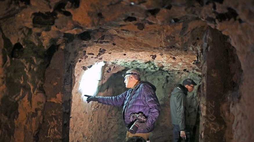 In this photo taken Friday Feb. 20, 2015,  Jeffrey Gusky, left, a photographer and physician from Texas points at graffitis in a former chalk quarry, at the Cite Souterraine, Underground City, in Naours, northern France. Gusky began photographing the site last December and has tallied 1,821 individual names: 731 Australians, 339 British, 55 Americans, a handful of French and Canadians and 662 others whose nationalities have yet to be traced.Standing at right is Cite Souterraine manager Matthieu Beuvin. (AP Photo/Remy de la Mauviniere)