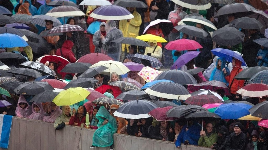 Faithful wait in the rain for Pope Francis' arrival to the Easter Mass in St. Peter's Square at the Vatican, Sunday, April 5, 2015.  (AP Photo/Alessandra Tarantino)
