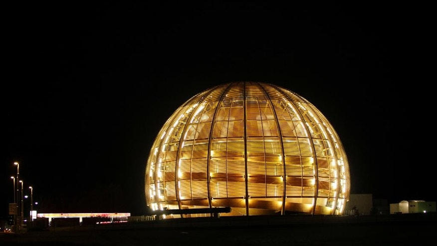 FILE - In this March 30, 2010 file picture the globe of the European Organization for Nuclear Research, CERN, is illuminated outside Geneva, Switzerland. The world's biggest particle accelerator is about to start up again after a two-year shutdown and upgrade. Scientists at the European Organization for Nuclear Research, or CERN, were preparing to shoot the first particle beams on Sunday April 5, 2015  through the Large Hadron Collider's 27-kilometer (16.8-mile) tunnel, beneath the Swiss-French border near Geneva.   (AP Photo/Anja Niedringhaus,file)