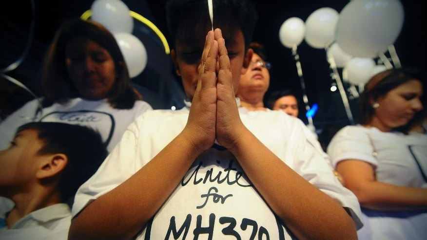 FILE - In this March 18, 2014 file photo, a young Malaysian boy prays at an event for the missing Malaysia Airlines Flight 370, at a shopping mall, in Petaling Jaya,  on the outskirts of Kuala Lumpur, Malaysia. A year of disasters, the disappearance of the flight and financial turbulence highlights the challenges confronting the world's biggest air travel market, where governments, regulators and airlines are struggling to keep up after a decade of astonishing growth. (AP Photo/Joshua Paul, File)
