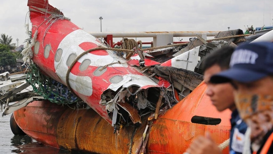 FILE - In this March 2, 2015 file photo, security guards stand near the newly-recovered remains of the fuselage of the ill-fated AirAsia Flight 8501 on the deck of rescue ship Crest Onyx at Tanjung Priok port in Jakarta, Indonesia. For Asia's aviation industry, the growing pains have just begun. A year of disasters, the disappearance of Malaysia Airlines Flight 370 and financial turbulence highlights the challenges confronting the world's biggest air travel market, where governments, regulators and airlines are struggling to keep up after a decade of astonishing growth. (AP Photo/Dita Alangkara, File)