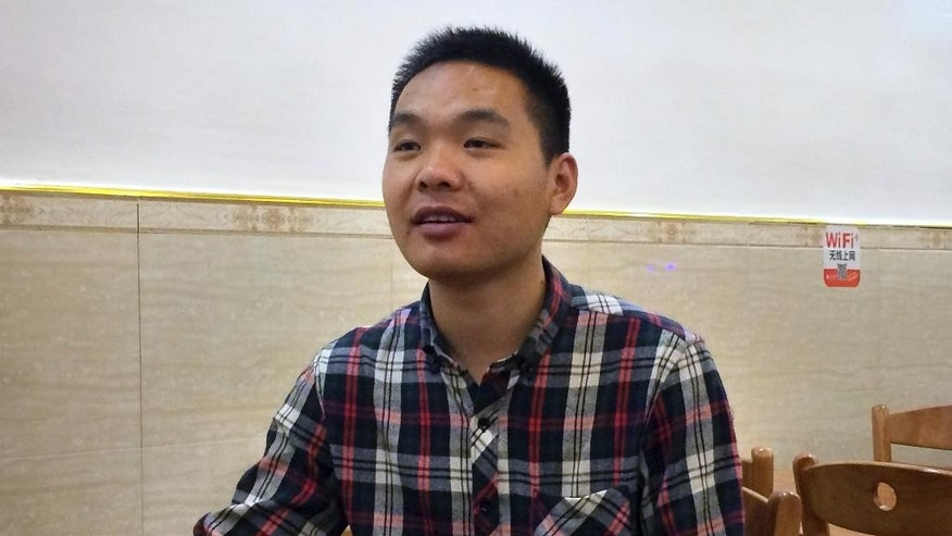 In this March 27, 2015 photo, Chinese labor leader Qi Jianguang sits in a restaurant in Shenzhen in southern China's Guangdong Province. In 2014, Qi, then 26, was the youngest of 13 representatives chosen by his fellow workers at a golf equipment plant to negotiate with management during a labor dispute. He and the others succeeded in having their demands met after a two-day strike, but Qi was fired seven months later over accusations that he smeared the company's reputation and engaged in an illegal strike. (AP Photo/Didi Tang)