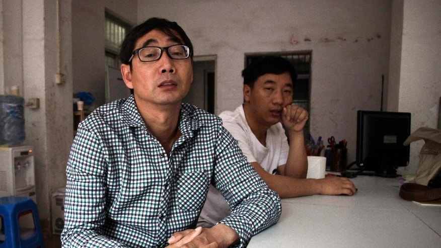In this March 28, 2015 photo, Chinese labor leader Wu Guijin, left, sits in an informal meeting hall in Shenzhen in southern China's Guangdong Province. Wu spent about a year in jail on a charge linked to his participation in a May 2013 strike but was eventually released without a conviction. He now devotes himself to helping workers learn their rights. (AP Photo/Didi Tang)