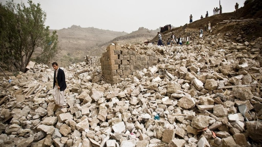 Yemenis stand amid the rubble of houses destroyed by Saudi-led airstrikes in a village near Sanaa, Yemen, Saturday, April 4, 2015. Since their advance began last year, the Shiite rebels, known as Houthis have overrun Yemen's capital, Sanaa, and several provinces, forcing the country's beleaguered President Abed Rabbo Mansour Hadi to flee the country. A Saudi-led coalition continued to carry out intensive airstrikes overnight and early Saturday morning targeting Houthi positions. (AP Photo/Hani Mohammed)