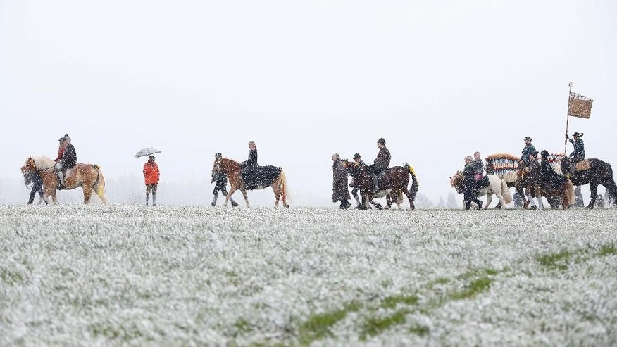 Local residents dressed in traditional Bavarian clothes of the region  ride through heavy snowfall  at the traditional Georgi (St. George)  horse riding procession on Easter Monday in Traunstein, southern Germany, Monday, April 6, 2015. (AP Photo/Matthias Schrader)