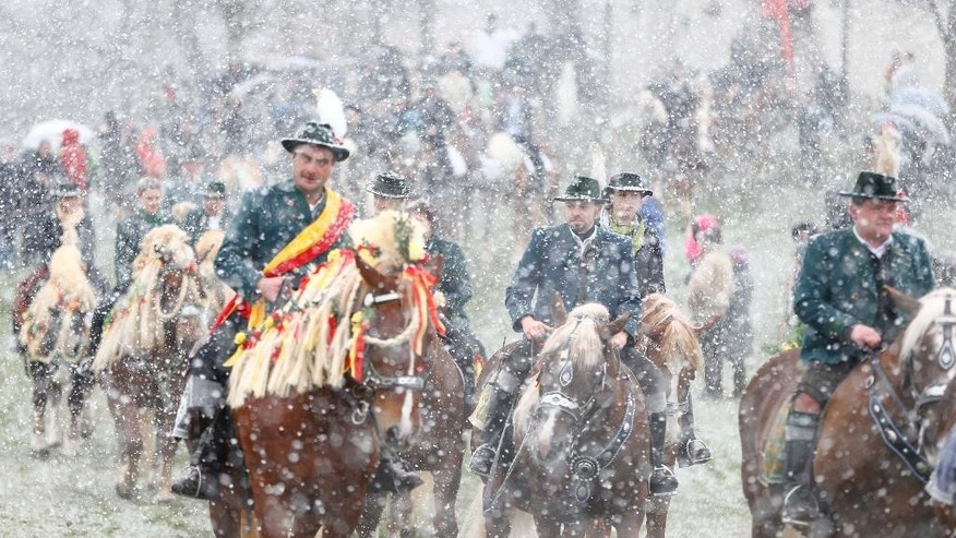 Local residents dressed in traditional Bavarian clothes of the region ride  during  heavy snowfall to get blessing for men and beast at the traditional Georgi  (St. George) horse riding procession on Easter Monday in Traunstein, southern Germany, Monday, April 6, 2015. (AP Photo/Matthias Schrader)