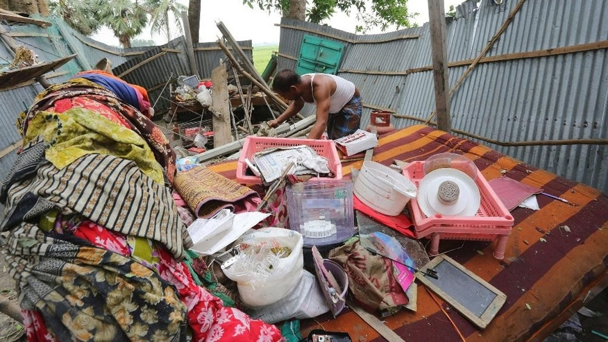 In this Sunday, April 5, 2015 photo, a Bangladeshi man tries to salvage his belongings after tropical storms damaged houses in Gabtoli area, in northern Bogra district, Bangladesh. Separate tropical storms that have swept through parts of Bangladesh have left dozens of people dead and scores injured. (AP Photo/Shafiq Islam)