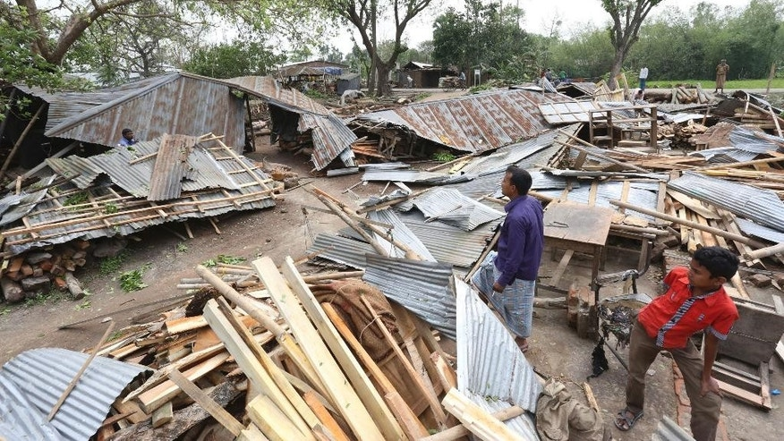 In this Sunday, April 5, 2015 photo, a Bangladeshi villagers inspect the scene after tropical storms damaged houses in Gabtoli area, in northern Bogra district, Bangladesh. Separate tropical storms that have swept through parts of Bangladesh have left dozens of people dead and scores injured. (AP Photo/Shafiq Islam)