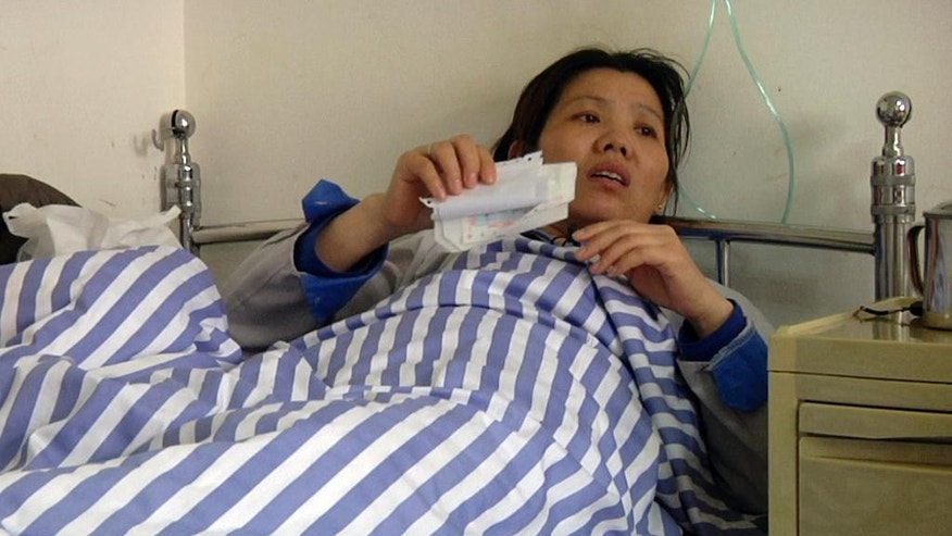 In this image taken from APTN video shot on March 26, 2015, Shi Jieying talks from her sickbed after she was hospitalized with heart trouble at Nanlang hospital in Zhongshan city in southern China's Guangdong Province. Timid by nature, Shi took a risk in March and joined fellow workers in a strike at her handbag factory, one of a surging number of such labor protests across China. (AP Photo/APTN)