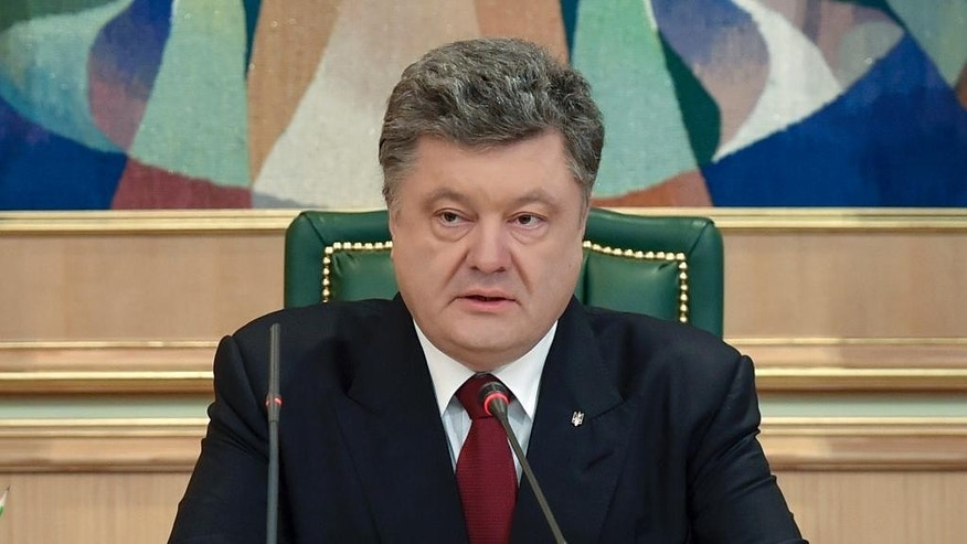 Ukraine's President Petro Poroshenko speaks to official in his office in Kiev, Ukraine, Monday, April 6, 2015.  Poroshenko on Monday April 6, 2015, publicly lifted his objections to a referendum that could give more powers to the restive regions engulfed in more than a year of warfare, reversing his government's previous position. (AP Photo/Mykola Lazarenko, Pool)