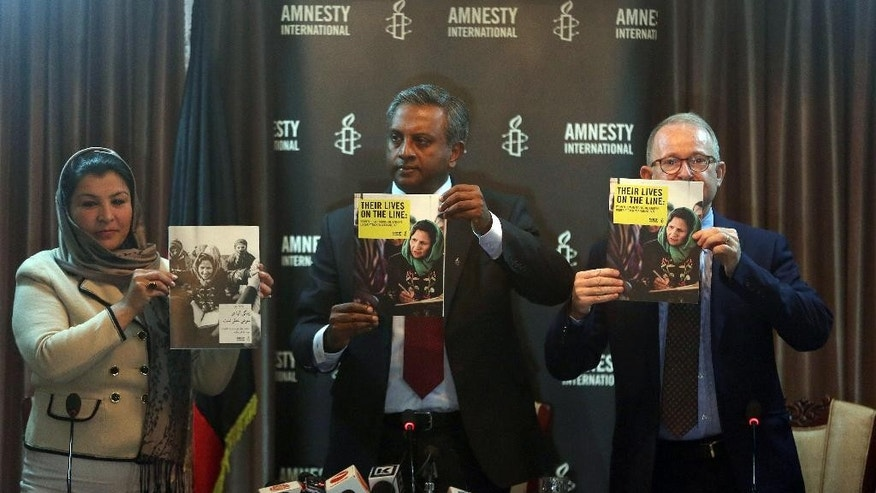 Amnesty International's Secretary General, Salil Shetty, center, and his colleagues show their new report on threats to Afghan women activists to local and international representatives during a press conference in Kabul, Afghanistan, Tuesday, April 7, 2015. Amnesty International says the activists, who are working to improve the human rights situation in their country, face increased violence, including threats, sexual assault and assassinations. (AP Photo/Massoud Hossaini)