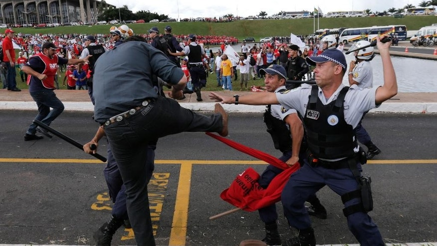 A demonstrator clashes with military police officers during a protest in Brasilia, Brazil, Tuesday, April 7, 2015. Thousands of workers have staged rallies in 12 cities across Brazil to protest against a proposed law that would allow companies to outsource their labor force. The biggest rally occurred in Brasilia where some 3,000 demonstrators gathered in front of Congress hours before lawmakers were expected to vote on the law. (AP Photo/Eraldo Peres)