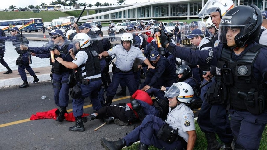 Military police officers keep back demonstrators with pepper spray as they detain a worker during a protest in front the Congress building, in Brasilia, Brazil, Tuesday, April 7, 2015. Thousands of workers have staged rallies in 12 cities across Brazil to protest against a proposed law that would allow companies to outsource their labor force. The biggest rally occurred in Brasilia where some 3,000 demonstrators gathered in front of Congress hours before lawmakers were expected to vote on the law. (AP Photo/Eraldo Peres)