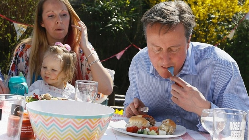 April 6, 2015: Britain's Prime Minister David Cameron has lunch with Lilli Docherty and her daughter Dakota in a garden with people who have benefited from tax and pension changes that became effective today, near Poole, southwest England.