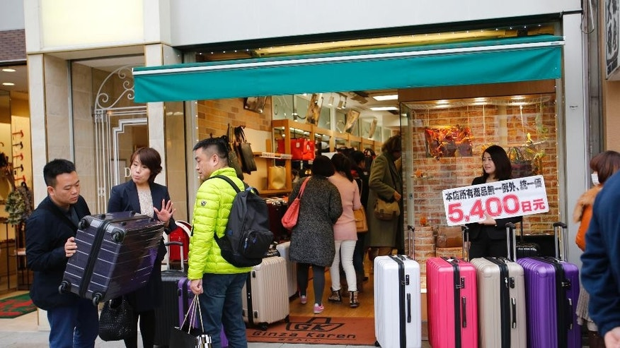 FILE - In this Nov. 17, 2014 file photo, Chinese shoppers check a suitcase at a bag shop posting a price tag in Chinese in Tokyo's Ginza shopping district.  China says it will try to convince its citizens to behave themselves while traveling abroad by requiring authorities back home to keep records of people doing anything illegal or inappropriate while in other countries.(AP Photo/Shizuo Kambayashi, File)
