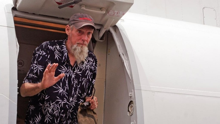 Released Dutch hostage Sjaak Rijke waves as he gets off an airplane after his recent release  in Bamako, Mali, Tuesday, April  7, 2015. French special forces on Monday freed a Dutchman held hostage since being kidnapped in 2011 by extremists in Mali, the government said. There was no word on the fate of two men abducted at the same time.  (AP Photo/Harouna Traore)