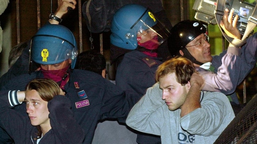 In this July 22, 2001 file photo, Italian riot police arrest unidentified anti-G8 protestors following a violent police raid in the A. Diaz school where they were housed during the Group of Eight (G8) meeting, in Genoa, northern Italy.  Europe's top human rights court said Tuesday, April 7, 2015, the unpunished police beating of 62-year-old Arnaldo Cestaro during July 2001 protests at the Genoa G-8 summit amounted to torture. The night of July 21-22, 2001, both Cestaro and a group of protesters were in a school when police stormed the building. The court said Cestaro raised his arms in surrender, but was beaten and kicked by the officers, suffering fractures and other injuries. (AP Photo/Luca Bruno, files)