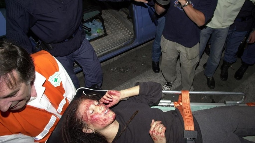 Sunday, July 22 2001file photoof a member of the Anti-globalization Genoa Social Forum, taken on a stretcher to an ambulance after a police raid inside the activists center in Genoa, Italy. Europe's top human rights court said Tuesday, April 7, 2015, the unpunished police beating of 62-year-old Arnaldo Cestaro during July 2001 protests at the Genoa G-8 summit amounted to torture. The night of July 21-22, 2001, both Cestaro and a group of protesters were in a school when police stormed the building. The court said Cestaro raised his arms in surrender, but was beaten and kicked by the officers, suffering fractures and other injuries.  (AP Photo/Marco di Lauro)
