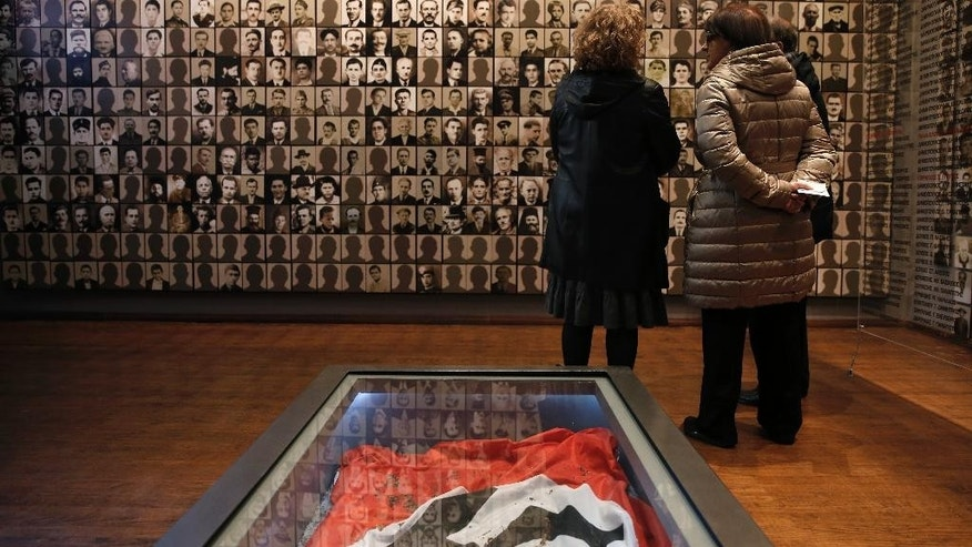 "In this photo taken on Saturday, March 21, 2015, visitors look at portraits of victims at the Holocaust Museum in the town of Kalavryta, western Greece, in front of a Nazi flag. Greek Defence Minister Panos Kamenos said Monday, April 5, that the country has obtained ""stunning evidence"" to support its massive claims for World War II reparations from Germany.(AP Photo/Petros Giannakouris)"