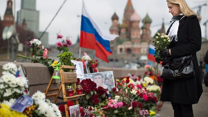 A woman lays a flower tribute at a place where Boris Nemtsov, a charismatic Russian opposition leader and sharp critic of President Vladimir Putin, was gunned down on Feb. 27, 2015 near the Kremlin in Moscow, Russia, Tuesday, April 7, 2015. Supporters of Russian opposition politician Boris Nemtsov gathered at a Moscow bridge where he was gunned down Feb. 27 to commemorate 40 days since his death, a special day in the Orthodox Christian tradition. (AP Photo/Alexander Zemlianichenko)