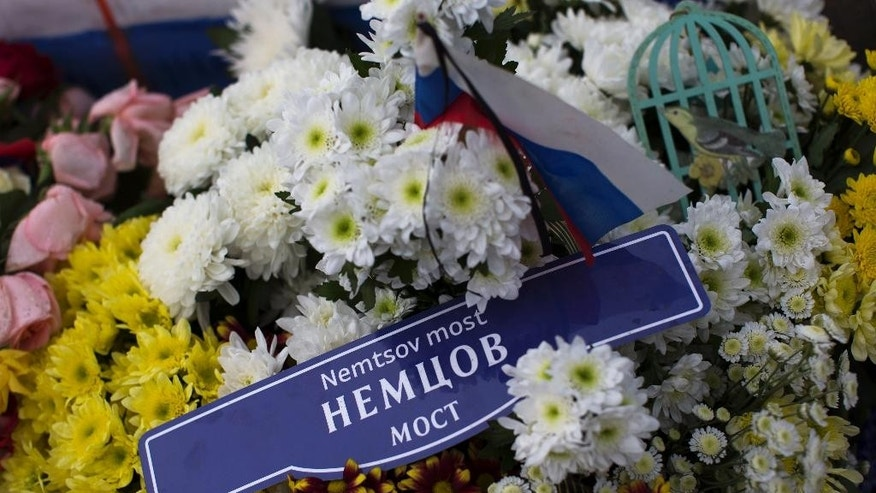 A mock street sign carrying Nemtsov's name is placed with flowers at a bridge, where Boris Nemtsov, a charismatic Russian opposition leader and sharp critic of President Vladimir Putin, was gunned down on Feb. 27, 2015 near the Kremlin in Moscow, Russia, Tuesday, April 7, 2015. Supporters of Russian opposition politician Boris Nemtsov gathered at a Moscow bridge where he was gunned down Feb. 27 to commemorate 40 days since his death, a special day in the Orthodox Christian tradition. (AP Photo/Alexander Zemlianichenko)