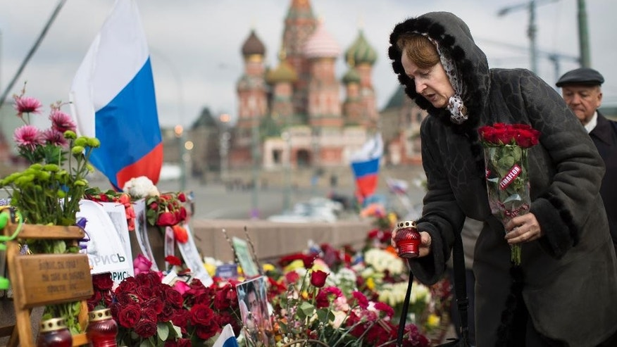 A woman lays a flower tribute and a votive candle at a place where Boris Nemtsov, a charismatic Russian opposition leader and sharp critic of President Vladimir Putin, was gunned down on Feb. 27, 2015 near the Kremlin in Moscow, Russia, Tuesday, April 7, 2015. Supporters of Russian opposition politician Boris Nemtsov gathered at a Moscow bridge where he was gunned down Feb. 27 to commemorate 40 days since his death, a special day in the Orthodox Christian tradition. (AP Photo/Alexander Zemlianichenko)