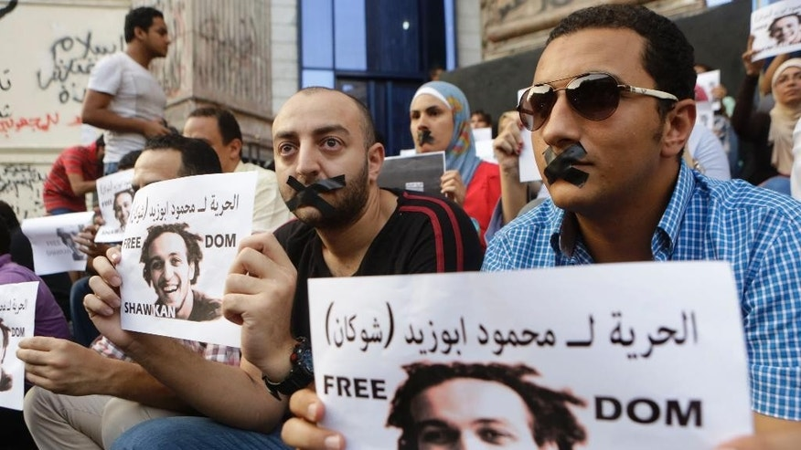 "FILE  - In this Saturday, July 12, 2014 file photo, Egyptian journalists tape their mouths and hold signs during a protest demanding the release from prison detention of Mahmoud Abu Zied, known as Shawkan, 27, in front of the Syndicate of Journalists building in Cairo, Egypt. Shawkan was arrested in August 2013 while taking photographs of the government's violent dispersal of a sit-in by supporters of ousted Islamist President Mohammed Morsi. Shawkan who has spent over 600 days locked up without any charges describes his prison as a ""cemetery"" and his indefinite detention as ""psychologically unbearable"" in a letter published by a rights group.  (AP Photo/Amr Nabil, File)"