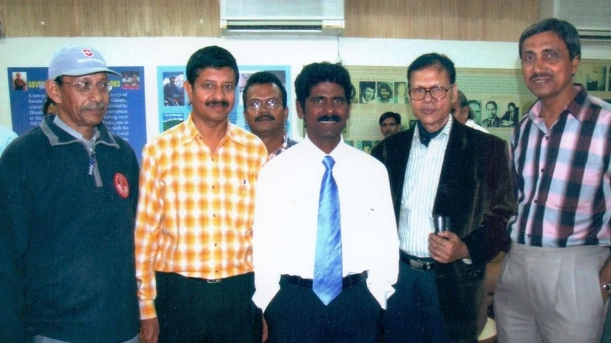 In this 2006 photo, Indian mountaineer Malli Mastan Babu, center, stands for a photograph with fellow climbers at an event in New Delhi, India. The well-known mountaineer from India has been found dead in the Andes after going missing since March 23, 2015 in the mountains on the border between Chile and Argentina. The mountaineer had achieved the feat of climbing the highest peaks on each of the seven continents. (AP Photo/Prosenjit Samanta)