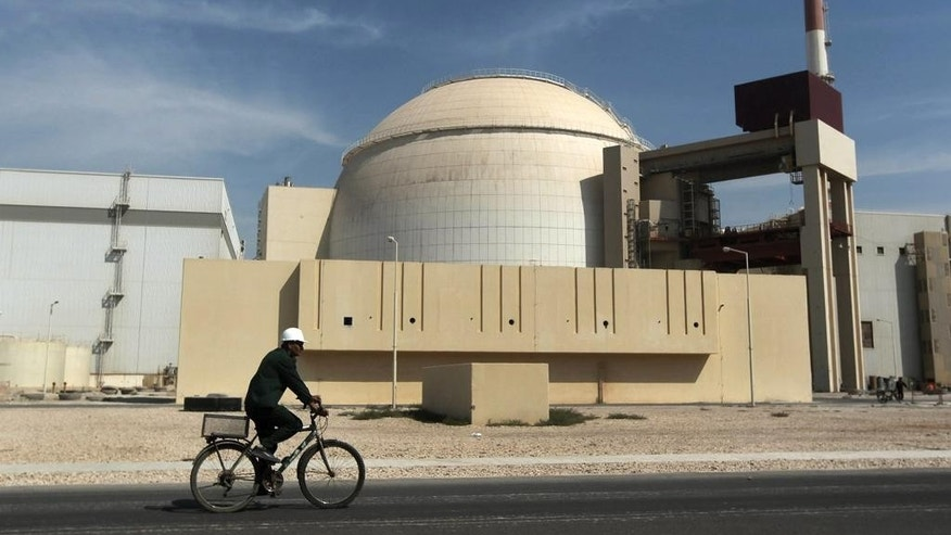 FILE - In this Oct. 26, 2010 file photo, a worker rides a bicycle in front of the reactor building of the Bushehr nuclear power plant, just outside the southern city of Bushehr.  Iran left the negotiating table in Lausanne, Switzerland, on Thursday, Aoril 2, 2015 with a commitment to implement the Additional Protocol, IAEA's most potent monitoring instrument. (AP Photo/Mehr News Agency, Majid Asgaripour, File)