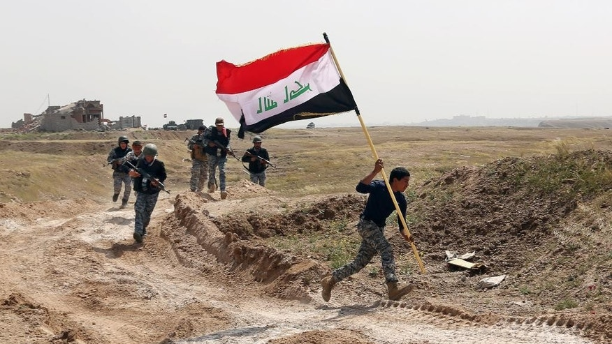 March 30, 2015: Amember of the Iraqi security forces running to plant the national flag as they surround Tikrit during clashes to regain the city from Islamic State militants, 80 miles north of Baghdad, Iraq.