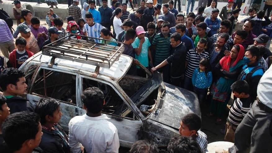 Nepalese people gather around the wreckage of a car burned by demonstrators during a general strike called by the alliance of 30 opposition parties, demanding the Himalayan nation's new constitution draft be passed by a national consensus, in Kathmandu, Nepal, Tuesday, April 7, 2015. A nationwide general strike enforced by opposition political parties has crippled life in Nepal, as protesters clashed with police and set vehicles on fire in the capital. The ruling coalition has been attempting to get the draft approved through a vote in parliament after negotiations failed with the opposition. (AP Photo/Niranjan Shrestha)