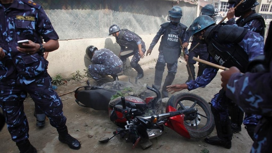 Nepalese policemen extinguish fire on a motorbike after it was vandalized by demonstrators during a general strike called by the alliance of 30 opposition parties, demanding the Himalayan nation's new constitution draft be passed by a national consensus, in Kathmandu, Nepal, Tuesday, April 7, 2015. A nationwide general strike enforced by opposition political parties has crippled life in Nepal, as protesters clashed with police and set vehicles on fire in the capital. The ruling coalition has been attempting to get the draft approved through a vote in parliament after negotiations failed with the opposition. (AP Photo/Niranjan Shrestha)