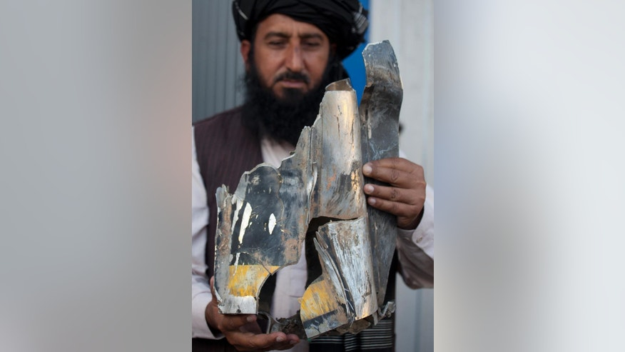 FILE - In this Thursday, Oct. 27, 2011 file photo, Pakistani tribal elder Karim Khan shows the remains of a missile reportedly fired by a U.S. drone on a village in north Waziristan, killing many people, after his news conference in Islamabad, Pakistan. A Pakistani judge on Tuesday, April 7, 2015, ordered criminal charges be filed against a former top CIA lawyer who oversaw its drone program and a former station chief in Islamabad over a 2009 strike that killed two people. Former acting general counsel John A. Rizzo and ex-station chief Jonathan Bank must face charges including murder, conspiracy, waging war against Pakistan and terrorism, Justice Shaukat Aziz Siddiqui of the Islamabad High Court ruled. (AP Photo/B.K. Bangash, File)